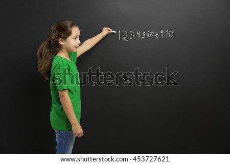 Smart little girl writing in a blackboard, with copy space