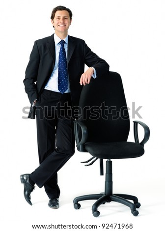 Smart looking businessman leans on an empty office chair to indicate an open position, suitable for recruitment campaigns - stock photo