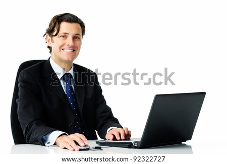 Smart looking man in a business suit smiles from on his laptop computer, isolated on white - stock photo