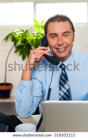 Smart male executive attending a call - stock photo