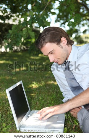 Smart male executive using a laptop with a blank screen in the park - stock photo