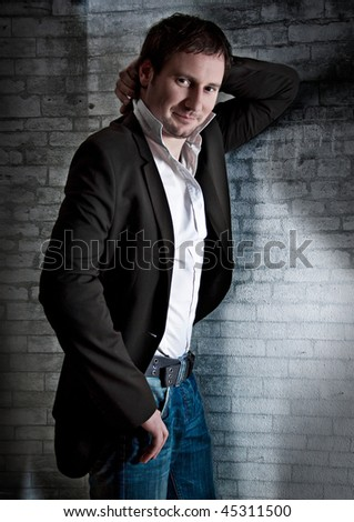 smart man leaning against a wall - stock photo