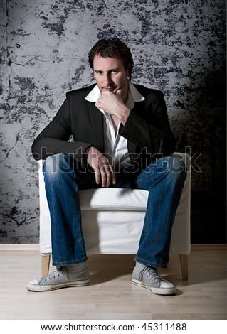 smart man sitting on an armchair - stock photo