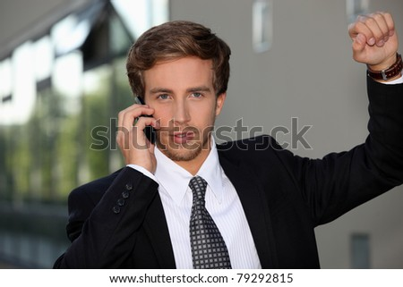 Smart man with phone leaning on a wall