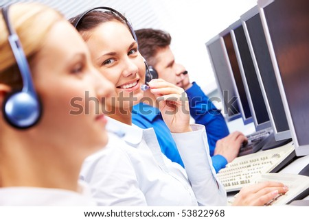 Smart operator sitting between co-workers during telephone conversation