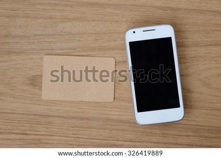 Smart phone and blank name card on wood background, top view - stock photo