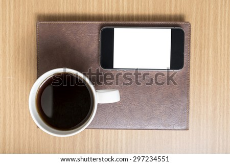 smart phone and coffee cup on book on wood background