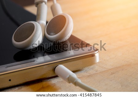 Smart phone and earphone on wooden table