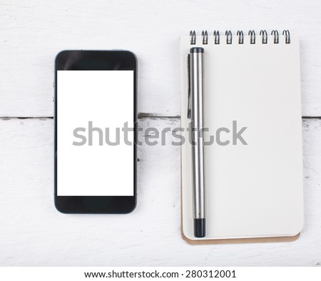 smart phone and note paper on wood table - stock photo