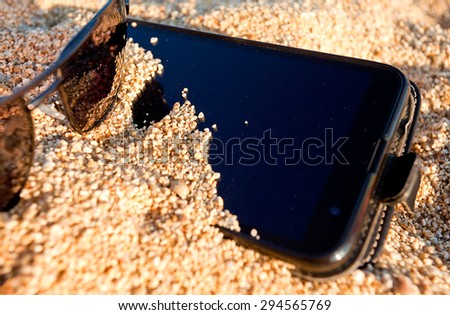 Smart phone and sunglasses buried in the sand. Concept for summer vacation on the beach.