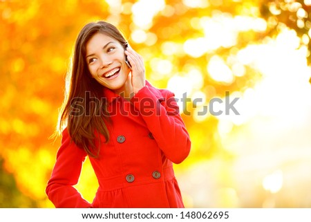 Smart phone Autumn woman talking on mobile phone in fall. Autumn girl having smartphone conversation in sun flare foliage. Portrait of mixed race Asian Caucasian young woman in forest in fall colors. - stock photo