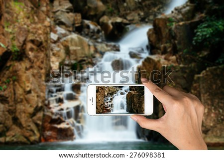 Smart phone camera taking photo picture of waterfall. Closeup of mobile phone camera screen photographing beautiful thailand landscape waterfall. - stock photo