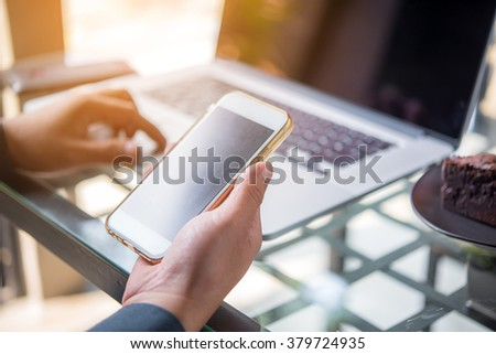 Smart phone in businessman hand with laptop
