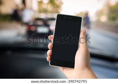 Smart phone in hand with car and road background, concept for insurance and transportation service business - stock photo