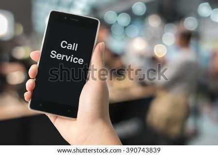 Smart Phone in hand with text call service on defocus of shop background, use for business concept - stock photo