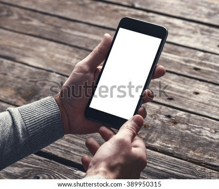Smart phone in male hands over table. Clipping path included. - stock photo