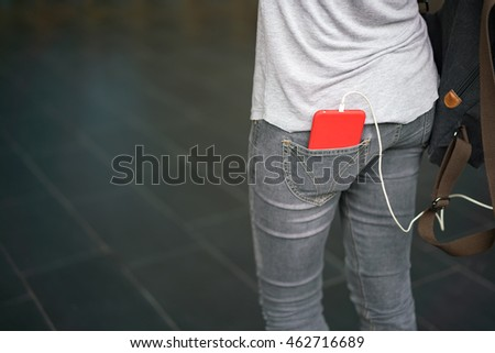 Smart phone in pocket of girl's jeans with copy space.