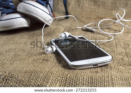 Smart phone on a table cloth with sneakers. Shallow depth of field. - stock photo