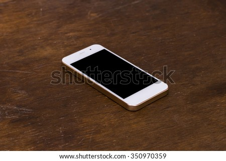 Smart Phone on the wooden table, which is off the screen - stock photo