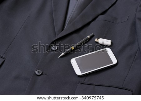 Smart phone, pencil and thumb drive on black suit. A man get ready to go to work.