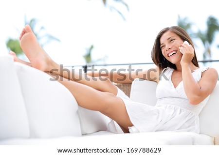 Smart phone - pretty woman mixed race asian caucasian talking on smart phone sitting relaxed on sofa smiling happy laughing having in white dress in couch relaxing with legs up at home. - stock photo