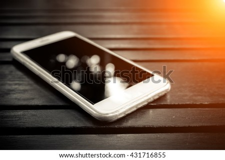 Smart phone with blank screen lying on wooden table, black and white Smart phone, Smart phone Mockup - Sunlight filter effect - stock photo