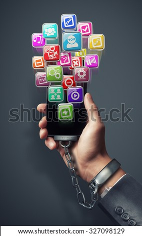Smart phone With color icons chained to handcuff in hand isolated on gray background. symbol for technology abuse. High resolution