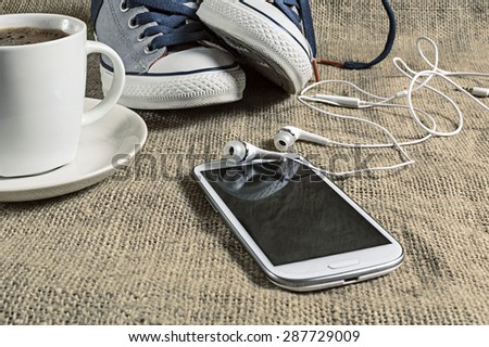 Smart phone with cup of coffee and sneakers. Shallow depth of field. - stock photo