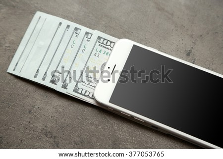 Smart phone with dollar banknotes on grey background. Making money online - stock photo