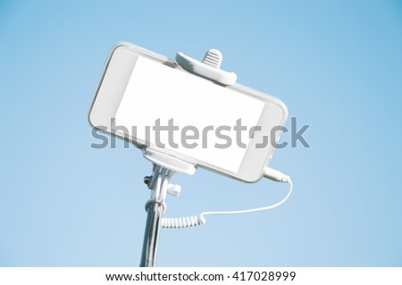 Smart phone with white blank copy space screen for your text or promotional content isolated against blue-sky background. Mobile phone on a selfie stick. Technology and communication concept
