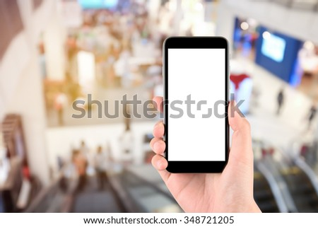 Smart phone with white screen in hand on blurred in shopping mall background - stock photo