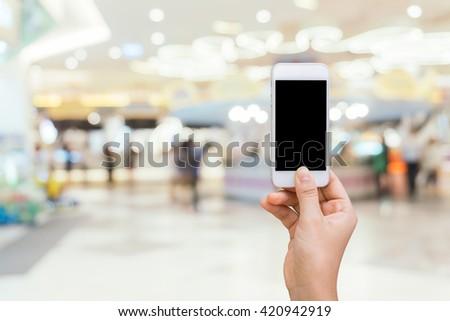 Smart phone with white screen in hand on blurred in shopping mall background,shopping online concept,shopping by smart phone - stock photo