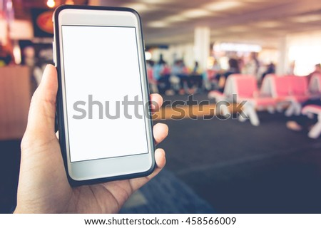 Smart phone with white screen in hand on blurred Seat airport  background - stock photo