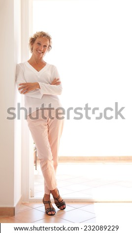 Smart professional business woman relaxing and leaning on a wall by a glass door with sunny light, relaxing and enjoying her aspirational lifestyle, interior. Home office with businesswoman standing. - stock photo
