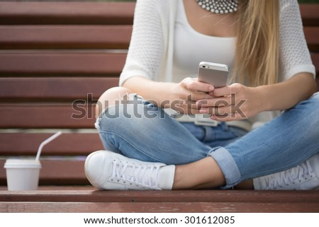 smart professional woman reading using phone. Female businesswoman reading news or texting sms on smartphone while drinking coffee on break from work.  - stock photo