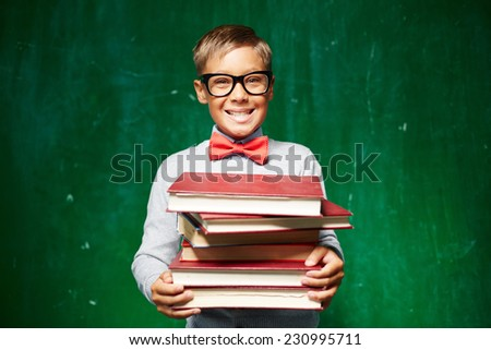 Smart pupil with textbooks looking at camera in isolation - stock photo