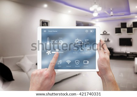 Smart remote home control system app. Living room interior in background. - stock photo