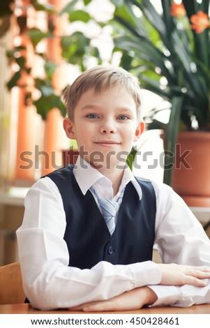 Smart schoolboy in school classroom - stock photo