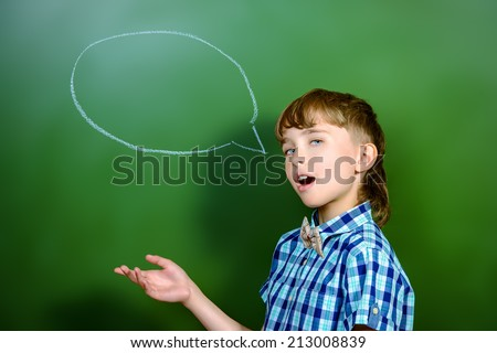 Smart schoolboy stands at the blackboard in the classroom. Education. New idea. - stock photo