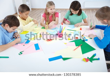 Smart schoolboys and schoolgirls drawing with colorful highlighters in classroom - stock photo