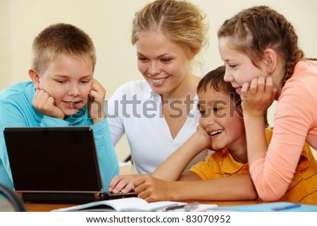 Smart schoolchildren and teacher working with laptop - stock photo