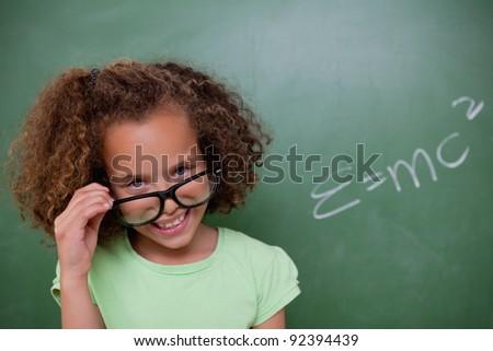 Smart schoolgirl looking above her glasses in front of a blackboard - stock photo