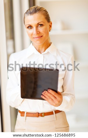smart senior businesswoman using tablet computer in office - stock photo