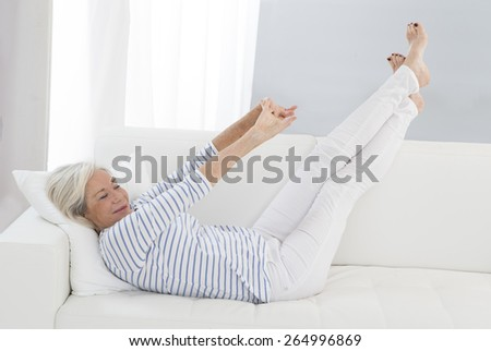 Smart senior  woman relaxing at home  legs lifted on the sofa -flexible, sporty - stock photo