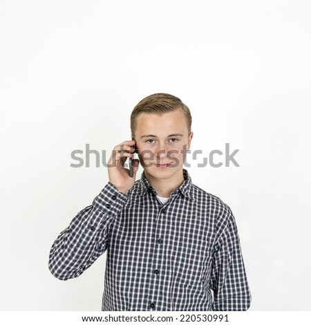 smart smiling boy uses his mobile phone - stock photo
