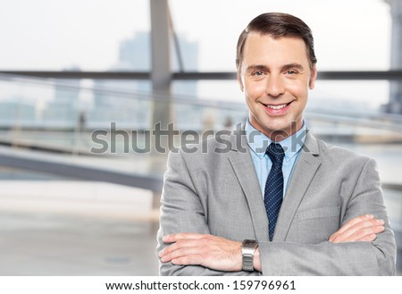 Smart smiling businessman posing confidently - stock photo