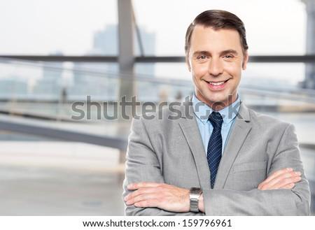 Smart smiling businessman posing confidently - stock photo