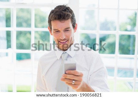Smart smiling young businessman text messaging at home - stock photo
