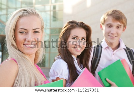 Smart students hold the books near college - stock photo