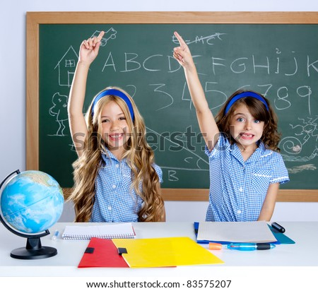 smart students in classroom raising hand with blackboard - stock photo